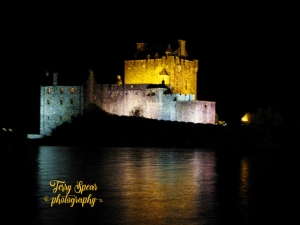 Eilean Donan castle night yellow and lights reflected off water text (640x480)